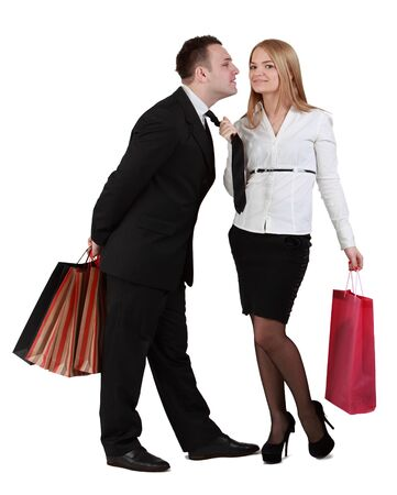 Image of a young couple with shopping bags having fun while the woman pulls her boyfriend tie for a kiss.