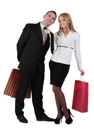 Image of a young couple with shopping bags having fun while the woman pulls her boyfriend tie. photo