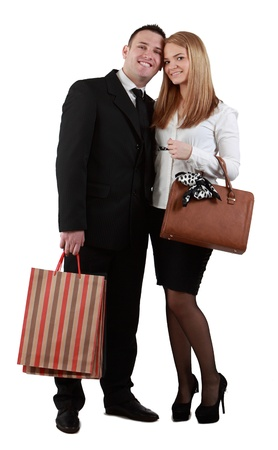 Happy young couple with shopping bags posing in a studio against a white background.