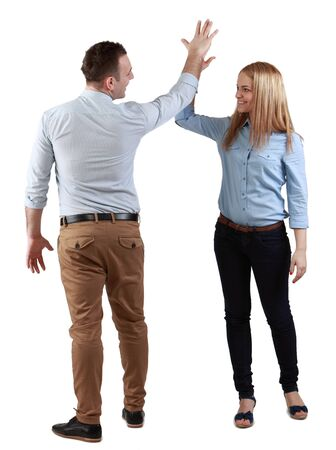 Happy young couple celebrating their success giving each other a high five, against a white background. photo