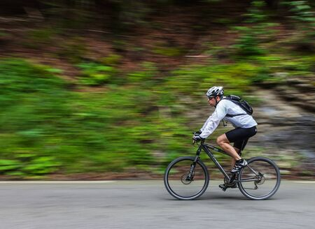 Gourette, France- July 15th, 2011: Image of an amateur cyclist going down on the road to Col D'abisuqe,in Pyrenees Mountains, before passing the peloton during the 13th stage of Le Tour de France 2011. Stock Photo - 13576085