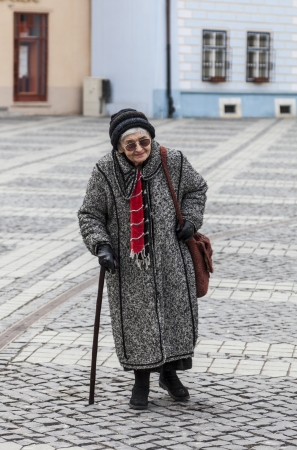 Image of a lonely senior woman walking in a paved city square. photo
