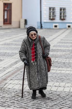 zpevněné: Obrázek osamělé starší žena chůze na dlážděné náměstí.