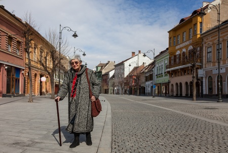 Image of a lonely senior woman walking in a paved city street. photo