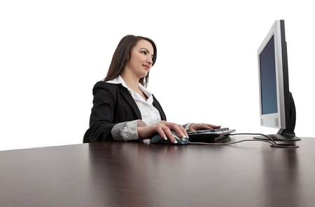 Image of a young brunette woman working on a computer at her desk, isolated against a white background. photo