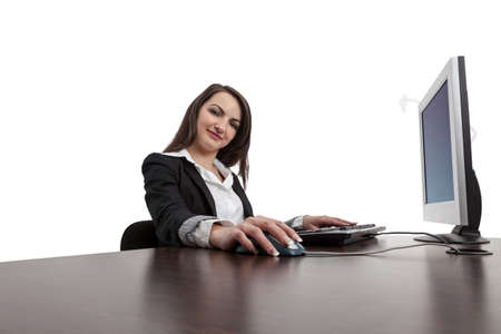 Image of a young brunette woman working on a computer while looking to the camera and smiling, isolated against a white background. Stock Photo - 13981834