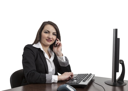 webdesigner: Image of a young brunette woman working on a computer and using a mobile phone , isolated against a white background.