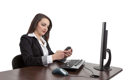 webdesigner: Image of a young brunette woman checking her mobile in front of the computer at her workplace , isolated against a white background.