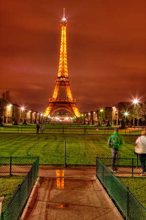 Paris,France- March 31st, 2012: Night image of the illuminated Eiffel Tower with a small reflection in a puddle on Champs de Mars.
