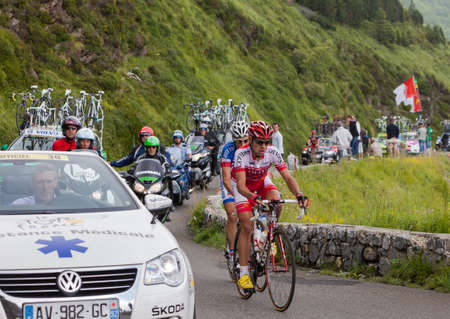 Beost,France,July 15th 2011: Image of two cyclists, cars and bikes climbing the last kilometers of the category H mountain pass Aubisque, during the 13th stage of Le Tour de France 2011.