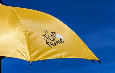 Paris,France,July 22,2012: Image of a yellow parasol with the official logo of Le Tour de France against a blue sky.During the Tour's days a lot of souvenirs are sold. Stock Photo - 14582162