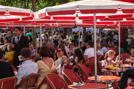des: Paris,July 22nd,2012:Image of people relaxing on a red terrace located on the crowded Avenue des Champs Elysees in Paris downtown.Avenue des Champs Elysees is the biggest and most famous and expensive boulevard in the world. Editorial
