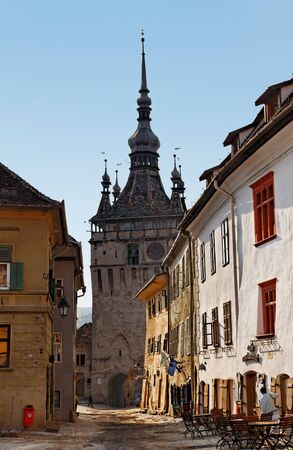 Sighisoara,Romania- July 24th, 2009: Image of a narrow street between the houses ending in front of the Clock Tower in Sighisoara citadel from Transylvania,Romania,Europe.Sighisoara is a beautiful and well preserved inhabited citadel in Europe,with an aut
