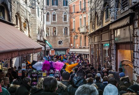 Venice,Italy- February 12,2012: Image of a crowd of people in a narrow street with souvenirs in Venice during the Venice Carnival days. Stock Photo - 14985993