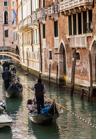 Venice,Italy- February 18, 2012: A row of gondolas sailing on a small canal in Venice during the Carnival days. Stock Photo - 14985995