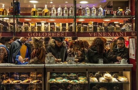Venice,Italy- February 18, 2012: People wearing various masks enjoy a coffee break in a small Venetian Cafe during the days of Venice Carnival.