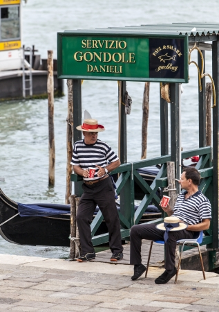 respite: Venice,Italy,July 30 2011: Image of two gondoliers having a respite moment in the evening, discussing and enjoying a cup of Cola near the Grand Canal on San Marco Square in Venice. Editorial