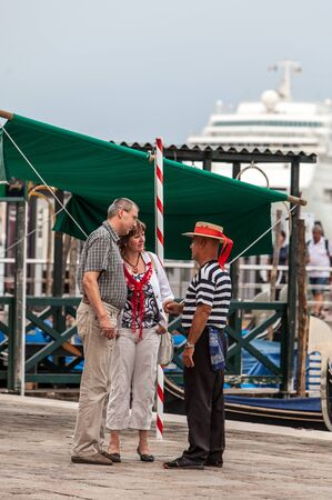 boatman: Venice,Italy,July 30 2011: Image of a gondolier negotiating with tourists in San Marco Square the price of a cruise in gondola on the Venetian canals. Editorial