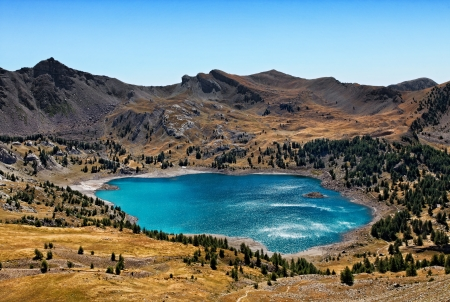 Image of Lac DAllos (2228 m) during a windy day with sunlight relections on the rippled water surface. This lake  is the largest natural lake (54 ha)  in Europe at this altitude.It is located in The South Alps (Alpes de Haute Provence) in The Mercantour  photo