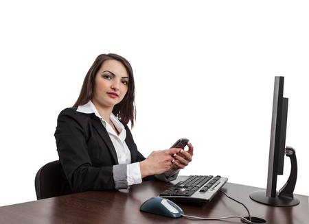 webdesigner: Image of a young brunette woman looking to the camera and checking her mobile in front of the computer at her workplace , isolated against a white background. Stock Photo