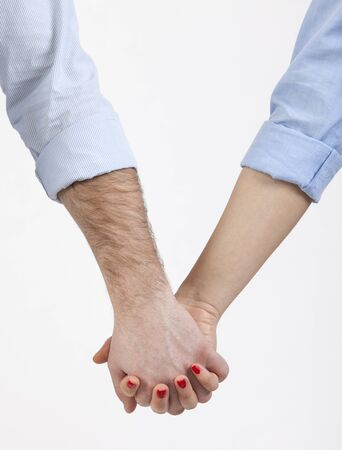 Close-up image of a couple holding hands with turned up sleeves. photo