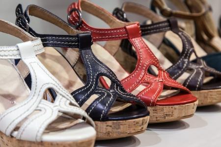sandalias: Una fila de sandalias de cuero femeninos coloridos en un estante de una tienda de zapatos.