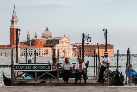 workmate: Venice,Italy,July 30 2011: Image of gondoliers having a respite moment at the end of the workday in the evening near the Grand Canal on San Marco Square in Venice.