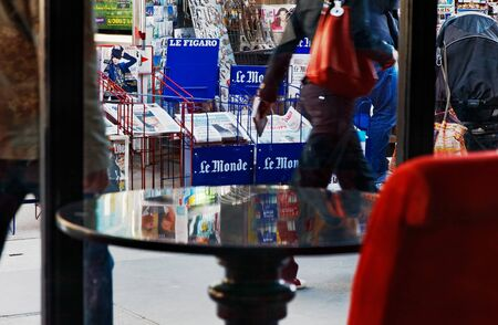 Paris,France- May 13th, 2012: Image of a street in Paris seen from a specific coffee terrace, with nice reflection on a empty table. Paris is one of the most visited city in the world with a lot of people walking in the streets everyday.