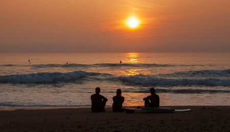 Image of the silhouettes of three surfers admiring the sunset at the coastline Stock Photo - 15424857