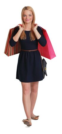 purchaser: Young blonde woman with two shopping bags walking to the camera against a white background. Stock Photo
