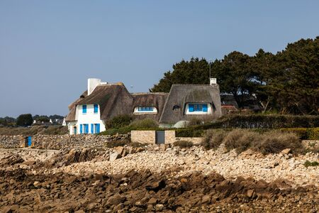thatched house: Carnac, France- March 25th, 2012: Image of a traditional stone house with blue shutters and thatched roof located on a rocky coastline in Brittany in northern France. Editorial