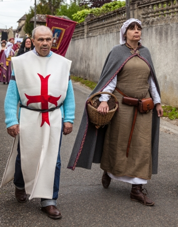 Nogent le Rotrou, France- May 19th, 2012:A couple of medieval characters with a traditional costumes marching during a parade near the Saint Jean Castle in Nogent le Rotrou,France, during a a historical reenactment festival.