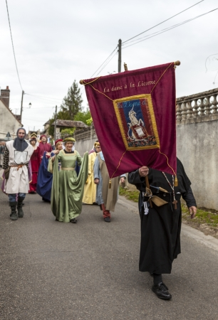 forerunner: Nogent le Rotrou, France- May 19th, 2012: Parade of medieval characters with a standard bearer forerunner marching near the Saint Jean Castle in Nogent le Rotrou,France, during a a historical reenactment festival.