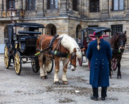 dam square: Amsterdam,The Netherlands- October 30, 2011: A coachman standing in front of two carriages with beautiful horses in Dam Square in Amsterdam. He is waiting for clients for a retro style touwn touristic tour. Editorial