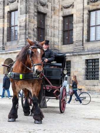 the coachman: Amsterdam,The Netherlands- October 30, 2011: Image of a carriage with a coachman making a retro style  town touristic tour in Dam Square in Amsterdam.