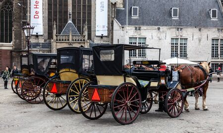 dam square: Amsterdam,The Netherlands- October 30, 2011: Unidentified tourists and a row of carriages parked in Dam Square in Amsterdam.