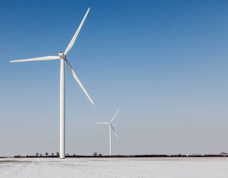 windturbines: Two windturbines on a field covered by snow in winter.