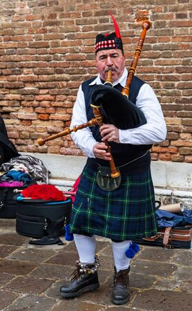 scotish: Venice, Italy-February 18, 2012: A traditional Scotish bagpiper perfoming in front of a brick wall in a sqaure in Venice during the Venice Carnival days.