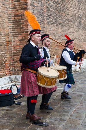 Venice, Italy-February 18, 2012: Traditional Scottish musical band performing in front of a brick wall in a square in Venice during the Venice Carnival days.
