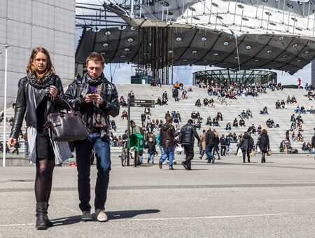 Paris,France,April 19th, 2012: Casual young couple walking through the camera in front of Le Grand Arche in La defense, the main business district of Paris.
