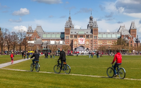 dutch landmark: Amsterdam, Netherlands- April 22, 2012: Three men riding their bicycles on a green yard in front of The New Rijksmuseum in Amsterdam.