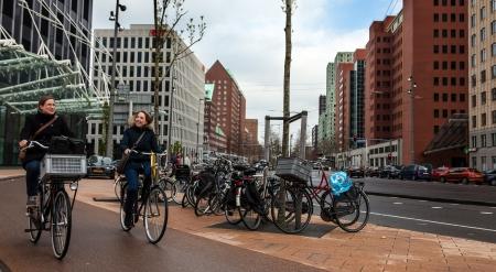 turismo ecologico: Rotterdam, Países Bajos, 24 de abril 2012: La imagen de dos imágenes de un dos mujeres felices jovenes que montan sus bicicletas en una calle de Rotterdam.