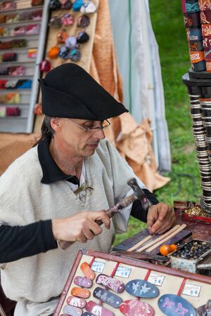 deftness: Nogent le Rotrou, France- May 19, 2012: Medieval leatherworker using a hammer at his workplace during a historical reenactment festival in Nogent le Rotrou, France.