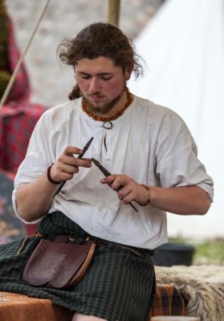craftsmanship: Nogent le Rotrou, France, May 15,2010: Portrait of a medieval Scottish jeweller working, during a historical reenactment festival in Nogent le Rotrou, France. Editorial