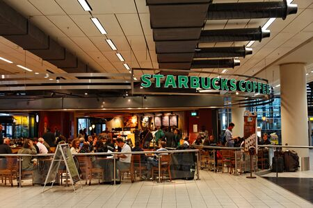 starbucks: Amsterdam,The Netherlands- October 31, 2011: People enjoying their breakfast on a Strabucks Coffee terrace in Schiphol Airport from Amsterdam. Starbucks is the largest coffeehouse company worlwide.