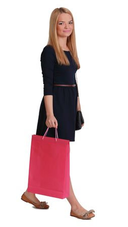 purchaser: Young blonde woman with a pink shopping bag walking against a white background. Stock Photo