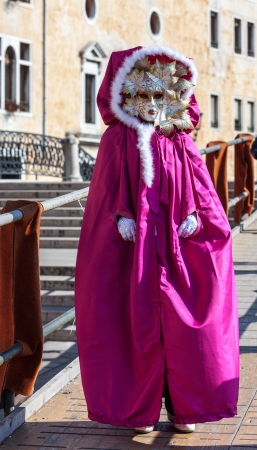 sestiere: Venice,Italy,February 26th 2011: Image of a person wearing specific pink costume and mask during The Carnival of Venice days.The Carnival of Venice (Carnevale di Venezia) is one of the world biggest annual festival, held in Venice, Italy.During the Carniv