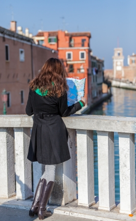 sestiere: Venice, Italy- February 26th, 2011: A young female tourist studying a map on a bridge on Sestiere Castello in Venice. Editorial