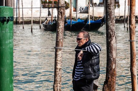 Venice, Italy- February 25th, 2011: Profile of a gondolier waiting for cliets on The Grand Canal in Venice.. Stock Photo - 16744397