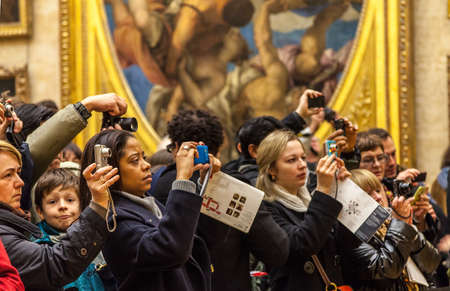 museum visit: Paris,France-  December 19, 2011: Image of a crowd of people using various digital devices to photograph important paintings (Mona Lisa by Leonardo da Vinci) in Louvre Museum in Paris.
